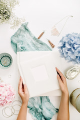 Woman hands hold family wedding photo album, pastel colorful hydrangea flower bouquet, turquoise blanket, decoration, fashion accessories on white background. Flat lay, top view.