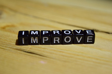 Improve written on wooden blocks. Inspiration and motivation concepts. Cross processed image on Wooden Background