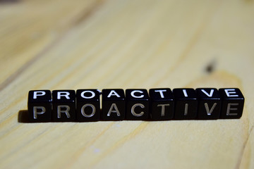 Proacive written on wooden blocks. Inspiration and motivation concepts. Cross processed image on Wooden Background