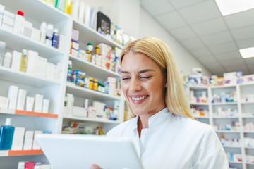 Cheerful pharmacist woman checking a medications on tablet at pharmacy drugstore