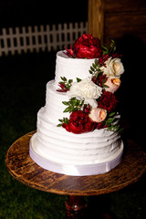 White wedding cake with red and white peonies flowers on it