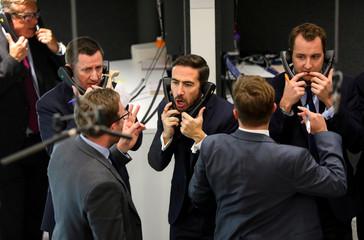 Traders work on the floor of the London Metal Exchange, in London