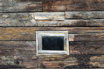 Old wooden wall with a window.