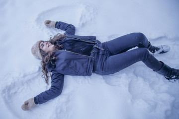 Happy young woman on snow as symbol of Christmas angel  (New Year, freedom, joy, winter season concept)
