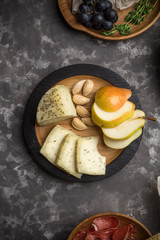 Closeup view of caciotta cheese with almond, pears on wooden plate on dark background