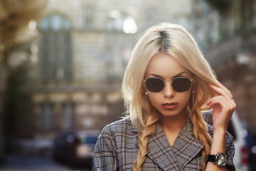 Outdoor close up fashion portrait of young beautiful woman wearing stylish sunglasses, wrist watch, tartan blazer. Model walking in street of european city. Copy, empty space for text