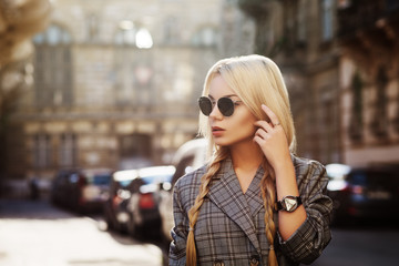 Outdoor close up fashion portrait of young beautiful woman wearing stylish sunglasses, wrist watch, gray tartan blazer. Model looking aside, walking in street of european city. Copy space for text