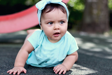 outdoor portrait of a beautiful baby on all fours. crawling on knees child on the floor