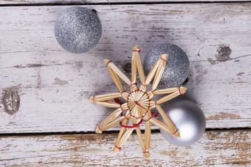 Silberne Christbaumkugeln auf rustikalem weißen Holz Hintergrund mit Christbaum und Sternen