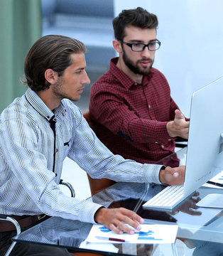 Two employees , sitting in front of computer