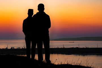 Lovers look to the sunset over the river