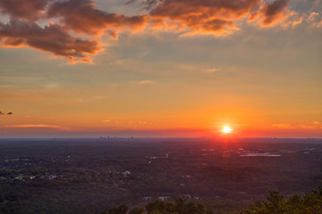 Beautiful orange, red, pink, yellow sunset with clouds and a blue sky looking out over the trees towards Atlanta, GA from Stone Mountain