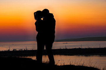 Lovers are kissing on a sunset over the river