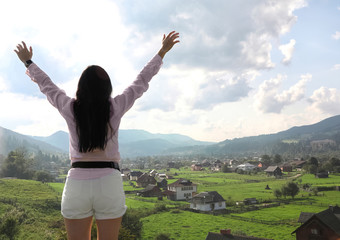 Young woman enjoying beautiful view of village in mountains