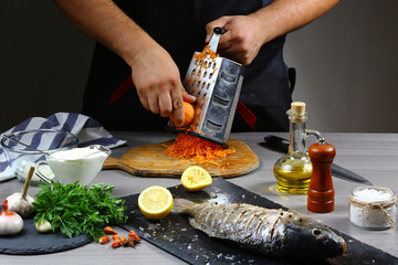 Cooking Carp Stuffed with Vegetables by chef hands, rub the carrots on a grater. cooking recipe. Authentic lifestyle image