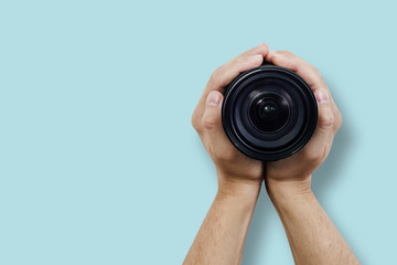 Top view of the camera lens held by hands. Hands braid the lens, top view on a pastel blue background. The concept of shooting, using photographic equipment. Photo courses.