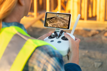 Female Unmanned Aircraft System (UAV) Quadcopter Drone Pilot with Controller Inspecting New House Framing