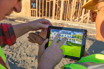 Male and Female Construction Workers Reviewing House on Computer Pad at Construction Site