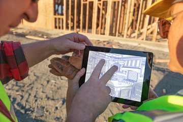 Male and Female Construction Workers Reviewing Kitchen Drawing on Computer Pad at Construction Site