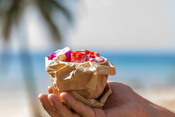 Pink strawberry ice cream in man's hand in front of beach with palm
