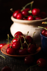 still life picture in the dark of fresh cherry on plate on wooden black background. fresh ripe cherries. soft focus image
