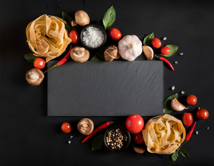 Fettuccine tagliatelle paste and slate board with mushrooms, herbs and spices