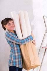 Pretty woman with wallpapers going to repair house