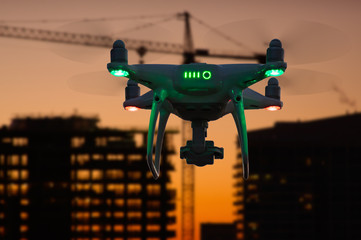 Silhouette of Unmanned Aircraft System (UAV) Quadcopter Drone In The Air Over Buildings Under Construction