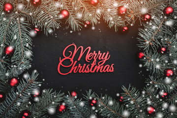 Black stone background with a frame of fir branches decorated with balls and red ribbon. Top view. With Merry Christmas text. Snow effect