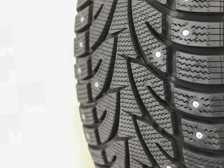 Studded tires. Winter tires with spikes close up. Detail of studded winter car tire