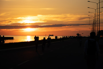 Sunset on the seaside promenade. Silhouettes of people walking on the road