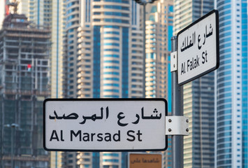 Two street signs with Arabic writings in front of a crowded background made of tall skyscrapers
