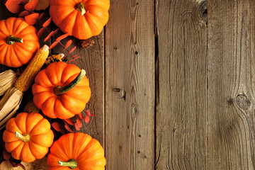 Autumn side border of pumpkins and fall decor on a rustic wood background with copy space