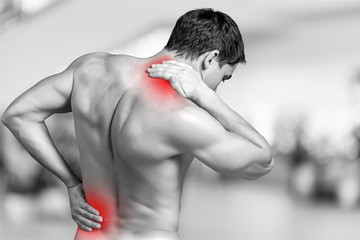 Strong man with neck pain, back view