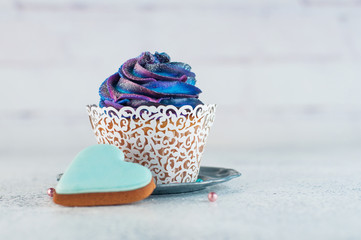 Cupcake with galaxy whipped cream on party background with copyspace