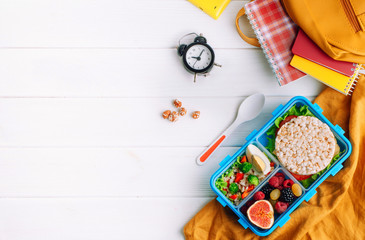 Foto op Canvas Assortiment Lunch box on white wooden background near school accessories