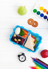 Lunch box with sandwich, vegetables, berries on white wooden background with clock and school accessories