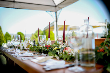 Chairs and table decorated with candles, served with cutlery and crockery and covered with a tablecloth. The table stands on a green lawn. Wedding Day