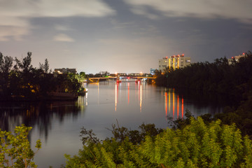Night time long exposure photo overlooking river and city in background. Skyline light illuminate water and drawbridge under evening clouds