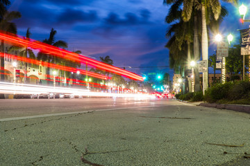 Night time long exposure of street traffic light trails in Delray Beach Florida as cars travel on road into downtown nightlife bar and resteraunt location Fotomurales