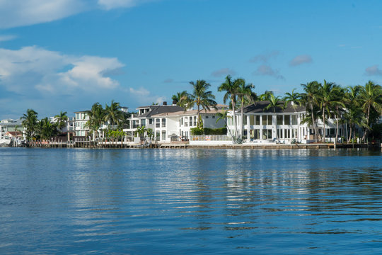 Day time exterior wide establishing shot of luxury mansion homes along inner coastal waterway river in Florida. Tropical vacation and summer home destination upper class living
