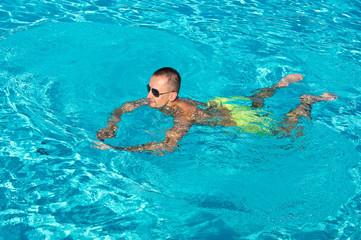 Young man enjoys swimming in outdoor pool
