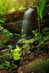 Traveler man taking a photo on Sai Fon (SAIFON) Waterfall in Tropical Rainforest Landscape at Phuhinrongkla National Park Nakhon Thai District in Phitsanulok, Thailand.