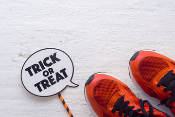 Happy Halloween Festival with sport shoes and trick or treat sign on white wood background