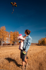 A young mother with her baby daughter enjoying nature and playing with a kite on a warm autumn sunny day in the background of a field and yellow trees.