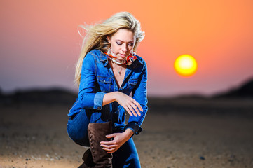 Portrait of beautiful blonde young woman in hat on the desert with sunset light.
