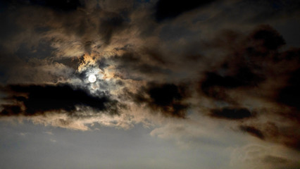 Sky with bright sun and dark clouds