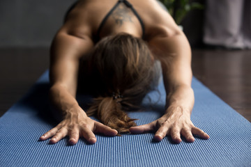 Young sporty woman practicing yoga, doing Child exercise, Balasana pose, working out, wearing sportswear, grey pants and top, indoor, body and hands close up, yoga studio