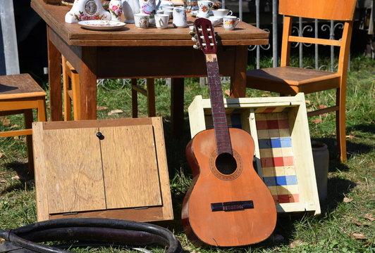 Flohmarktstand mit allerlei Trödel, Gitarre, Möbeln und Geschirr