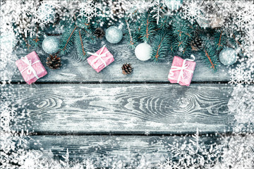 Christmas  winter holiday background with gifts boxes with fir branches, pine cones, New Year balls on wooden table. Flat lay, top view with copy space, texture wall with snowflakes and snow effect